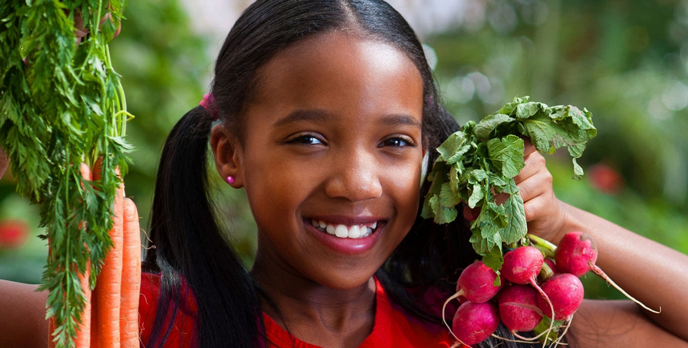 Girl holding radishes and carrots