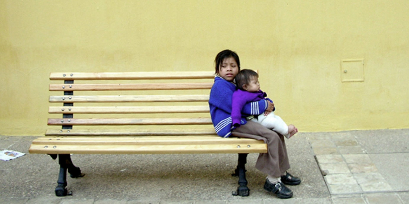 Child sitting on bench holding baby